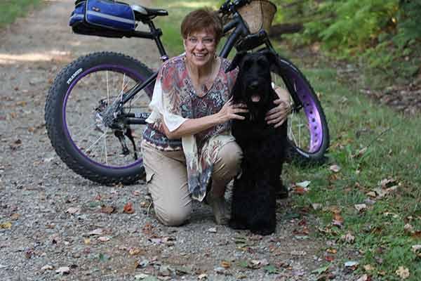 Lourdes and dog Sasha on the trail with her bike